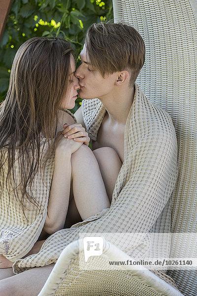Romantisches junges Paar in Decke gewickelt auf Hängestuhl im Freien