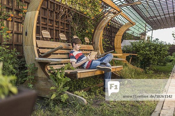 Volle Länge des Jungen mit digitalem Tablett während er auf der Bank im Garten sitzt