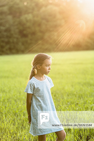 Nachdenkliches Mädchen  das auf einem grasbewachsenen Feld steht.
