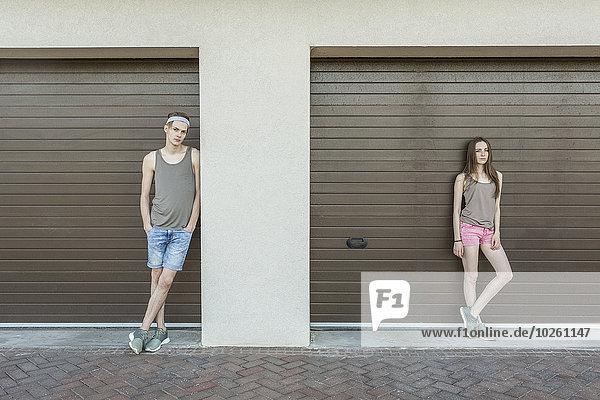 angelehnt,Garage,geschlossen,jung,Mann und Frau
