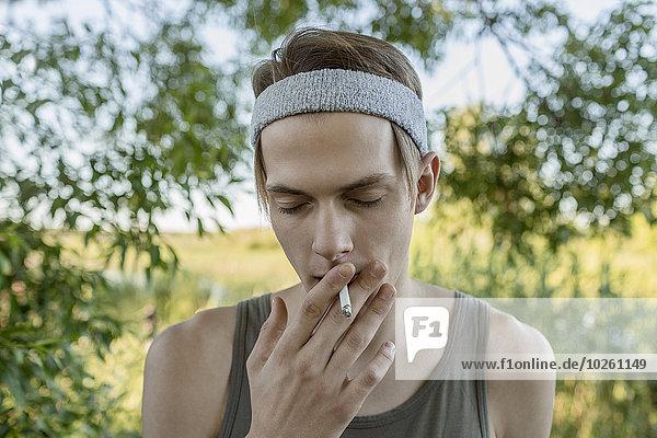 rauchen,rauchend,raucht,qualm,qualmend,qualmt,Außenaufnahme,Mann,jung,freie Natur