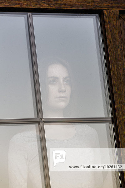 Nachdenkliche junge Frau schaut durchs Fenster