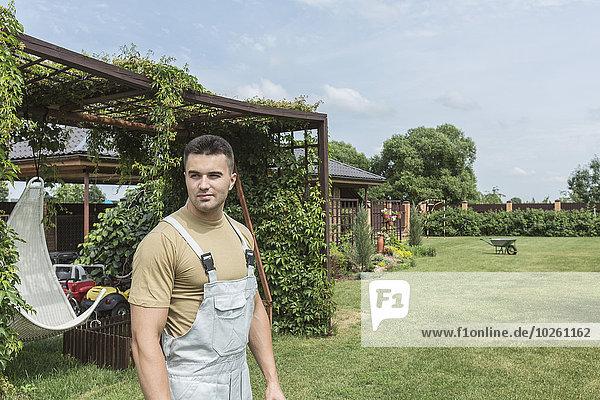 Junger Mann mit Latzhose im Hinterhof