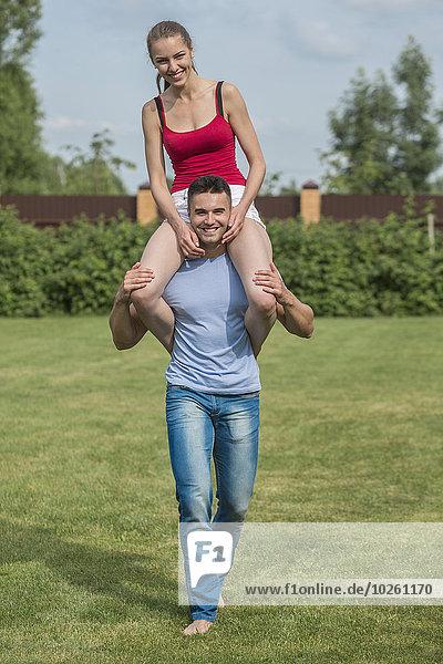 Ganzflächiges Porträt eines glücklichen jungen Mannes mit einer Frau auf den Schultern im Hinterhof.