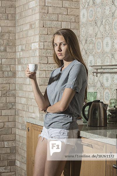Porträt einer schönen jungen Frau beim Kaffeetrinken auf dem Küchentisch