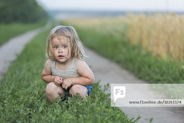 Porträt eines süßen Mädchens  das auf Pflanzen hockt.