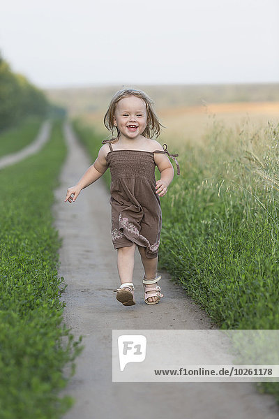 Ganzflächiges Porträt eines glücklichen kleinen Mädchens  das auf einem Naturlehrpfad spazieren geht.