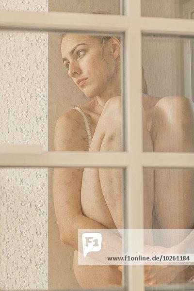 Nachdenkliche junge Frau sitzt auf dem Fensterbrett und schaut weg.