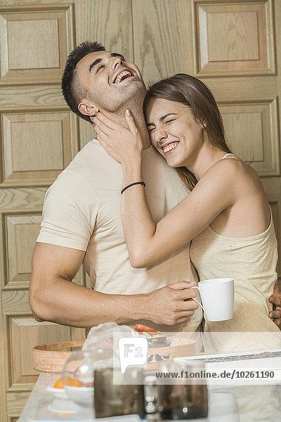 Fröhliches junges Paar  das sich in der Küche umarmt