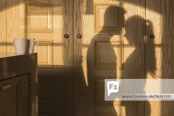 Schatten eines romantischen Paares auf einer Holzwand