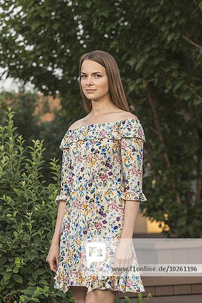 Porträt der schönen jungen Frau im Kleid im Freien