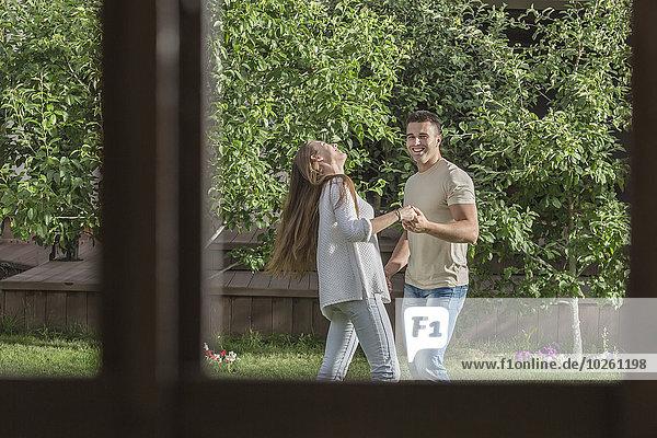 Ein glückliches junges Paar  das im Garten Händchen hält.
