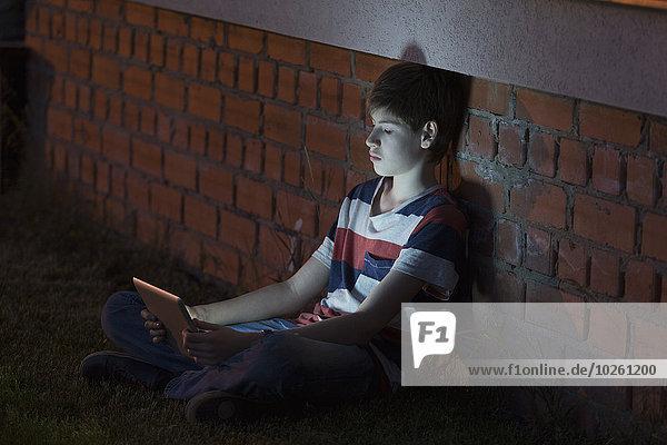 Junge mit digitalem Tablett beim Anlehnen an die Ziegelwand