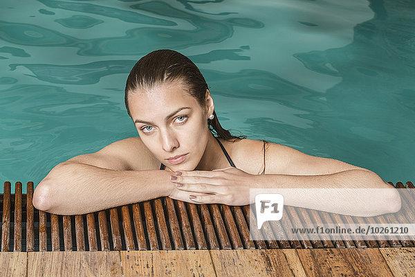 Porträt einer schönen jungen Frau  die sich am Rande des Swimmingpools entspannt.