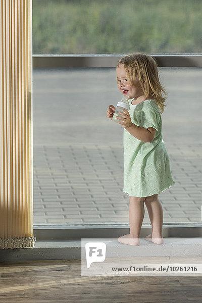 Volle Länge des Mädchens  das die Babyflasche hält  während es am Fenster steht.