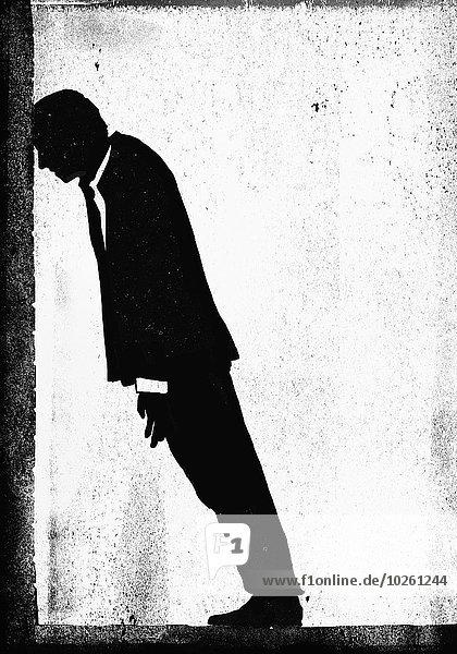 Illustratives Bild eines depressiven Geschäftsmannes  der sich an die Wand lehnt.