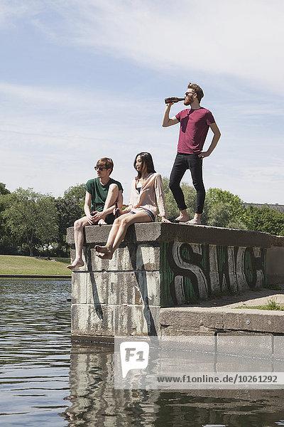 Multiethnische Freunde bei Bier an der Stützmauer am Kanal