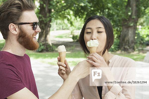 Glücklicher Mann füttert Frau im Park mit Eiscreme
