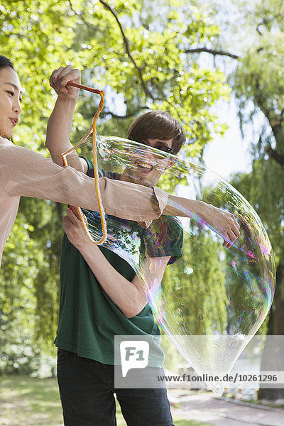 Happy man putting friend's hand in big bubble at park