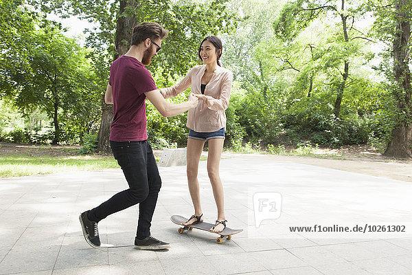 Junger Mann assistiert Frau beim Skateboarden auf dem Fußweg im Park