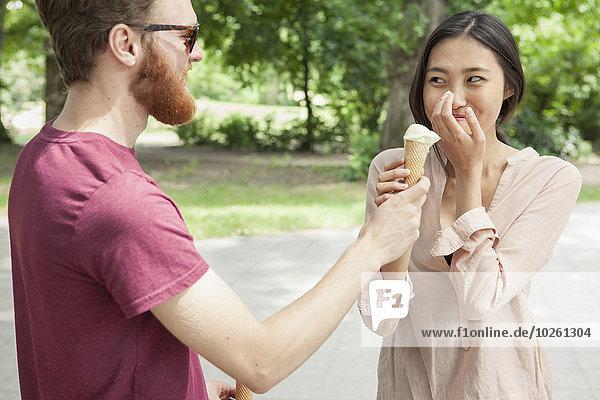 Glückliche Frau sieht den Mann an  der im Park Eis hält.