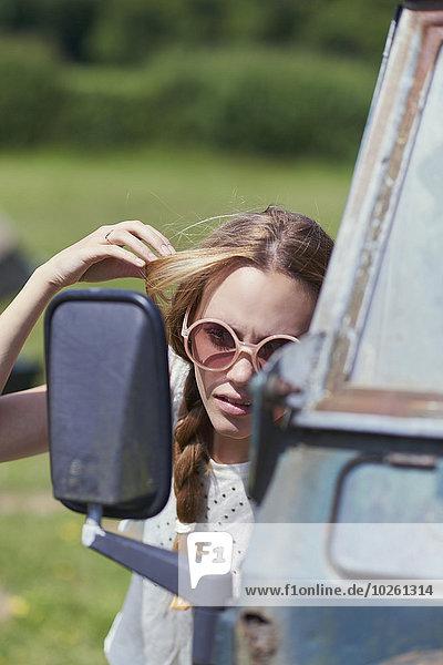 Junge Frau macht Haare beim Anblick des LKW-Seitenspiegels