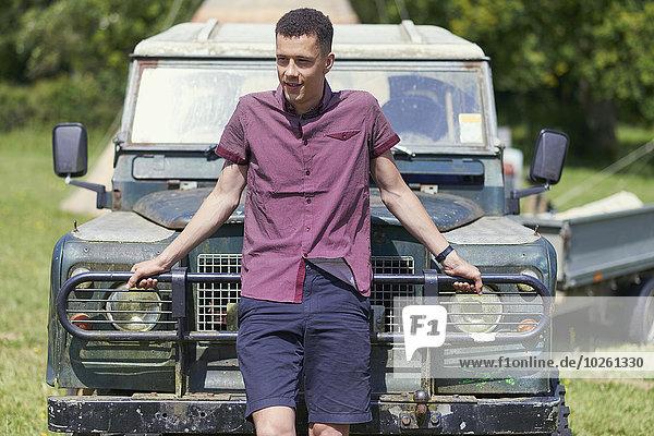 Junger Mann  der sich im Park auf einen Lastwagen stützt.