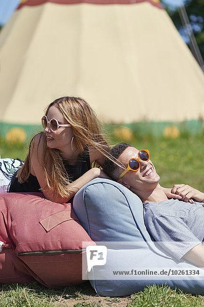 Fröhliches Paar auf Kissen liegend  im Hintergrund Teepee