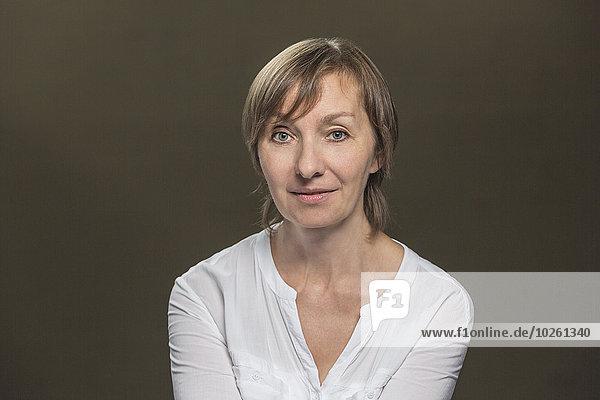 Porträt einer selbstbewussten reifen Frau über grauem Hintergrund