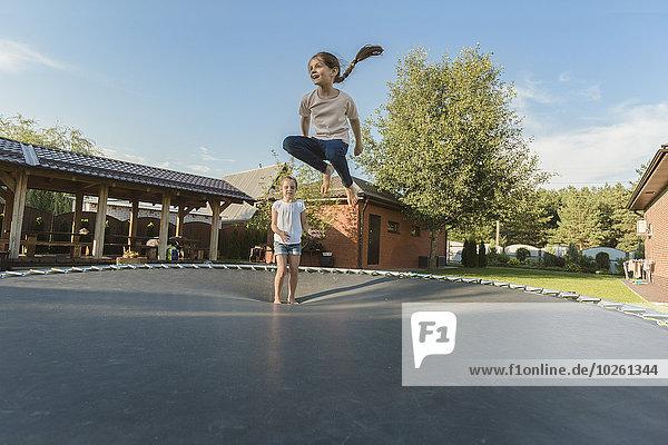Mädchen mit Schwester beim Springen auf Trampolin im Hof