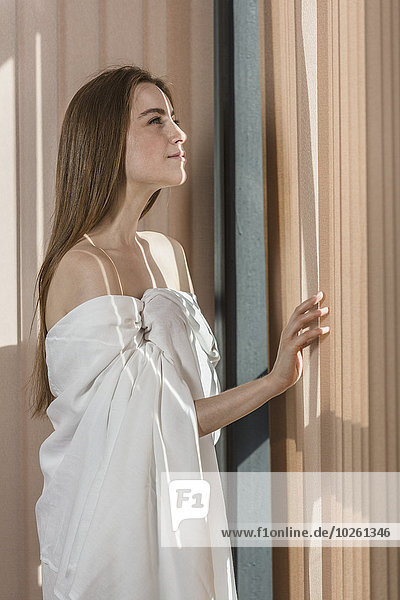Sinnliche junge Frau in Laken gewickelt  die durchs Fenster schaut.