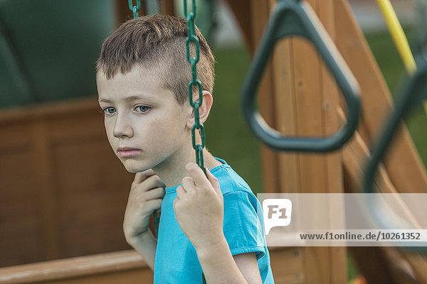 Nachdenklicher kleiner Junge  der im Hof schwingt.