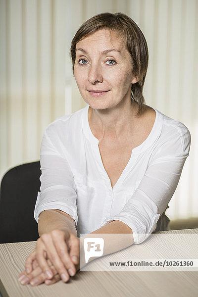 Porträt einer selbstbewussten reifen Frau  die am Tisch sitzt