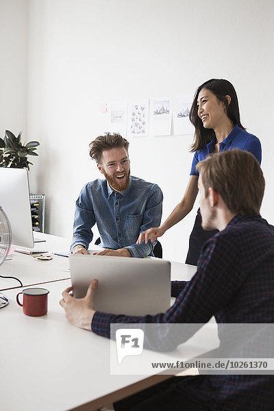 Glückliche Geschäftsleute kommunizieren am Schreibtisch im Büro