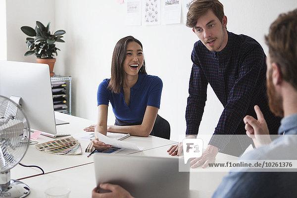 Junge Geschäftsleute diskutieren im Büro