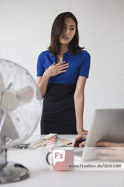 Junge Geschäftsfrau kommuniziert am Schreibtisch