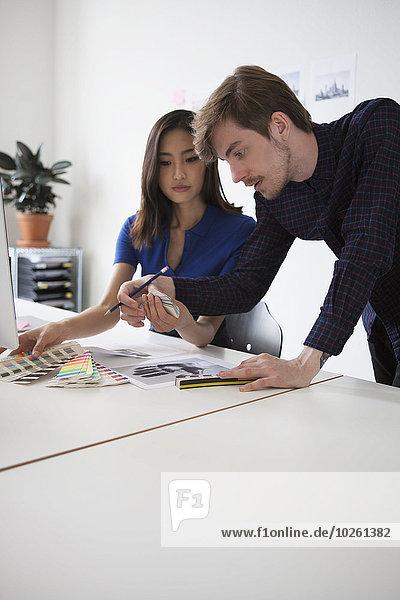 Junge Geschäftskollegen diskutieren über Muster am Schreibtisch