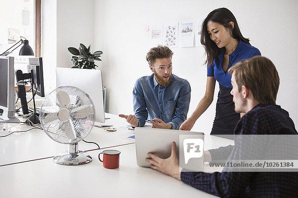 Multiethnische Geschäftsleute kommunizieren am Schreibtisch im Büro