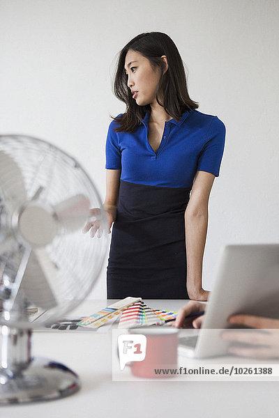Junge Geschäftsfrau bei der Präsentation am Schreibtisch