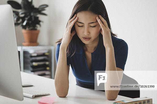 Junge Geschäftsfrau mit Kopfschmerzen am Schreibtisch im Büro