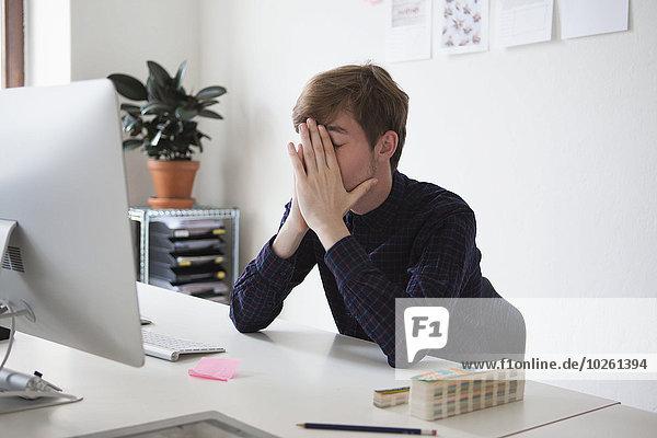 Müde Geschäftsmann mit den Händen auf dem Gesicht am Schreibtisch