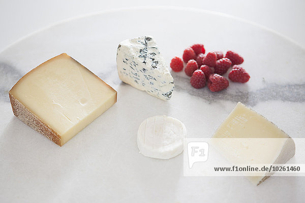 Käse und Himbeeren im Teller auf weißem Grund