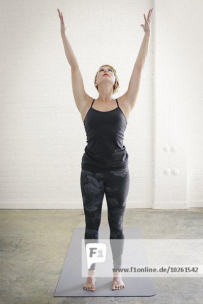 stehend Frau Zimmer schwarz Yoga Turnanzug blond Leggins Matte