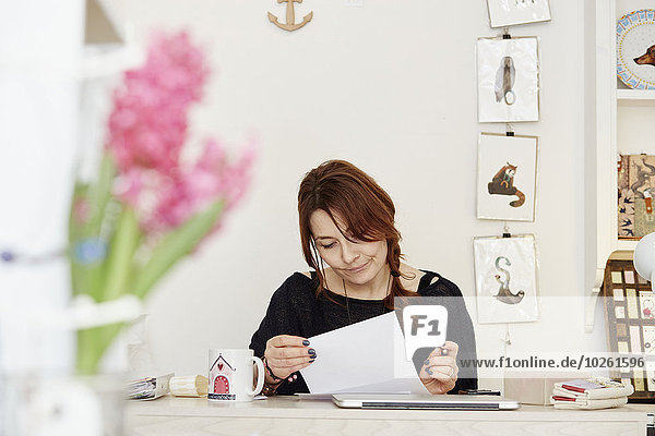 A woman sitting at a desk in a small gift shop  doing the paperwork  managing the business. A laptop on the desk.