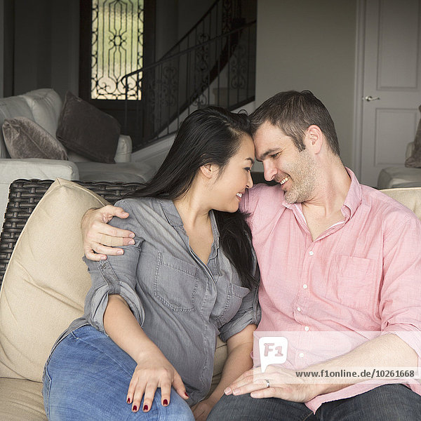 Smiling man and woman sitting on a sofa  hugging  and looking at each other.