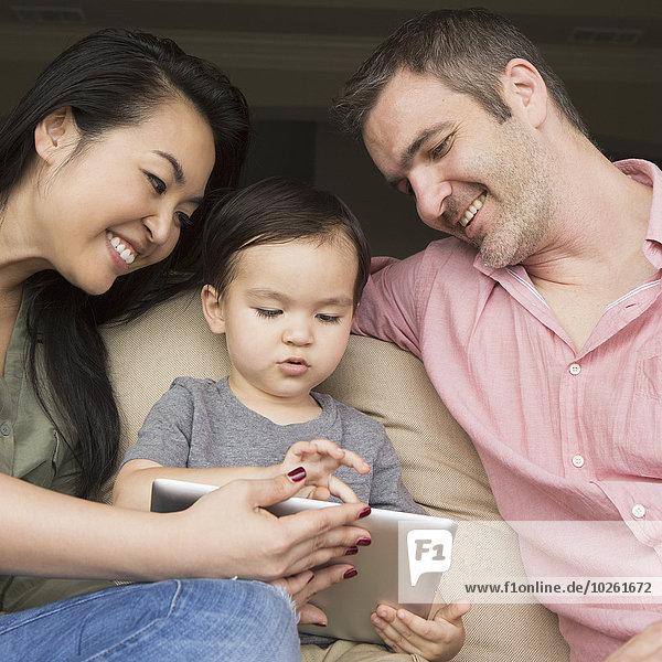 sitzend sehen Couch Sohn Menschliche Eltern jung Tablet PC