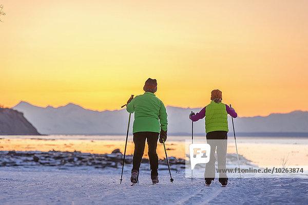 beleuchtet überqueren Mensch zwei Personen Menschen Sonnenuntergang folgen Küste Skisport 2 Kreuz