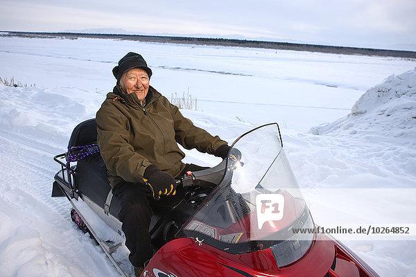 Außenaufnahme Winter Mann sitzend Maschine Alaska Ethnisches Erscheinungsbild Holunder Schnee