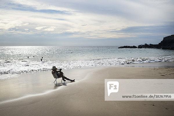 Frau sitzend Buch Stuhl Ecke Ecken Strand Sonnenuntergang Mexiko Taschenbuch vorlesen