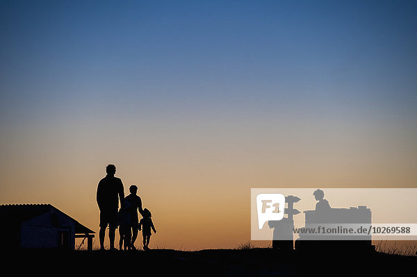 Silhouette of a family standing and watching the sunset; Cabo Polonio  Uruguay